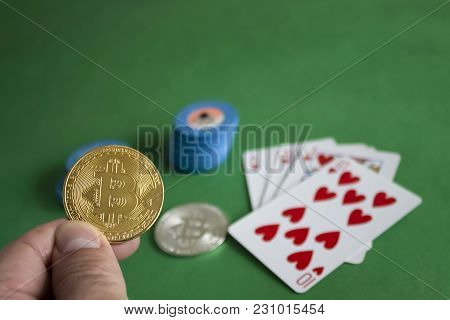 Two Bitcoins Laying Down On Green Poker Table And Bunch Of Chips With Cards In The Background|gold|s