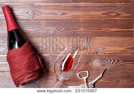 Photo Of Bottle Of Wine, Corkscrew, Wine Glass On Brown, Wooden Background
