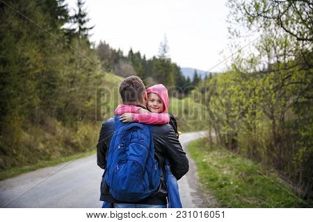 Young father and his adorable little daughter hiking in mountains in beautiful sunny day