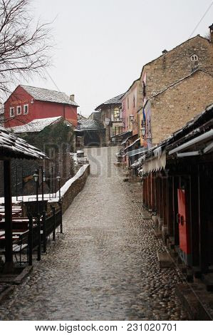 Mostar Old Town Street With Shops And Historic Architecture In Winter. Cloudy Weather