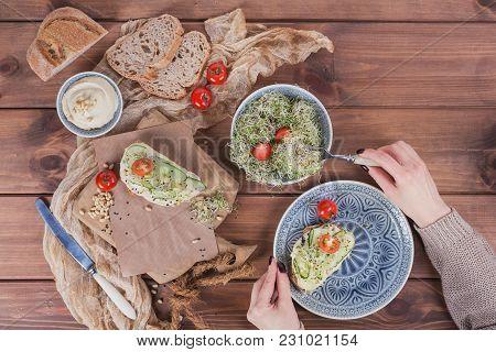 Preparing Healthy Vegetarian Bruschettas With Bread, Micro Greens, Hummus, Cucumbers And Pine Nuts O