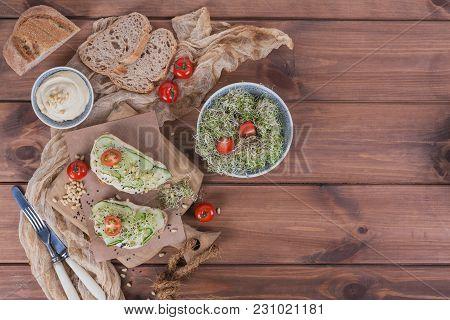 Healthy Vegetarian Bruschettas With Bread, Micro Greens, Hummus, Cherry Tomatoes, Cucumbers And Pine