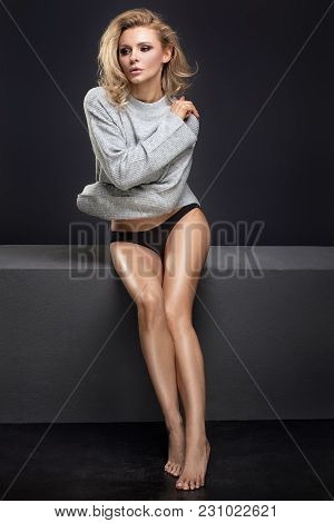 Sensual Female Model Posing In Fashionable Sweater. Blonde Beautiful Woman With Glamour Makeup And L