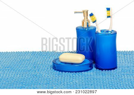 Blue Glass With Toothbrushes, Dispenser For Liquid Detergent And Soap Dish With White Soap. Isolated