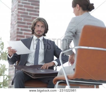 A relaxed conversation of a man and a woman in the office