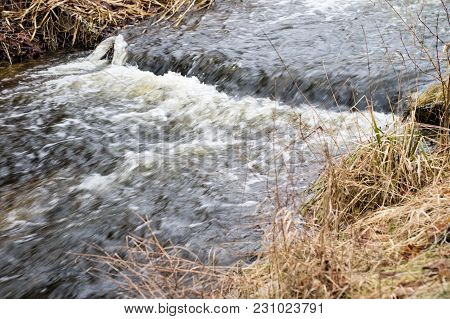 Water Threshold On A Small River In The Forest. Waterfall On A Narrow Watercourse.