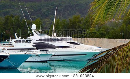 Four White Expensive Yachts Anchor In The Harbor Of The Seychelles With Turquoise Water And The Gree