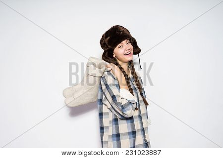 Happy Beautiful Young Russian Girl In Fur Hat Holds Gray Felt Boots In Hands, Laughs