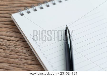 Closed Up Of Black Pen On List Of Numbers With Lines On White Clean Paper Notepad On Wooden Table In