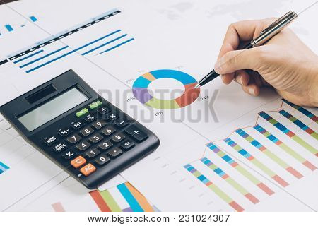 Finance, Business Budget Planning Or Analysis Concept, Hand Holding Pen Reviewing Pie Chart And Grap