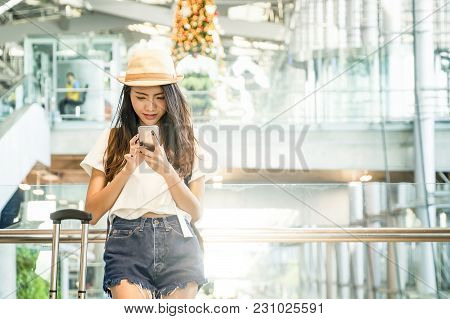 Young Woman In Airport Waiting For Air Travel Using Smart Phone. She Is Sitting With Travel Suitcase