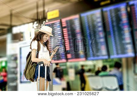 Young Woman With Backpack And Carry On Luggage In International Airport, Near Flight Information Boa