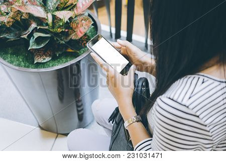 Woman Relaxing While Using Smart Phone Blank Screen For Graphics Display Montage. Over The Shoulder