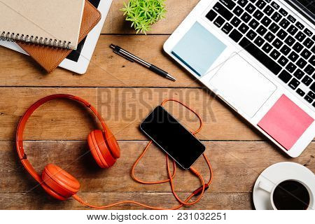 Office Desk Table With Laptop,smart Phone,pen,headphone,notebook And Cup Of Coffee.flat Lay Photo.to
