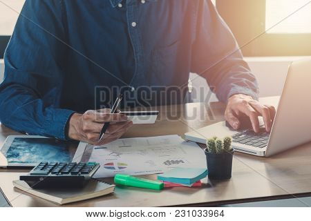 Man Using Credit Card And Office Desk Table With Computer, Supplies And Coffee Cup.online Payment Co