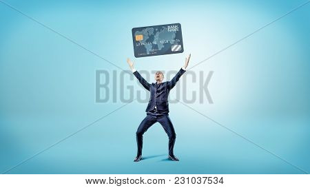 A Happy And Victorious Businessman Stands On A Blue Background And Holds Up A Giant Generic Credit C