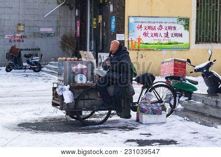 Hunchun, Jilin, China - March 8, 2018: A Seller Of Potatoes On The Street Sells A Sweet Grilled Pota
