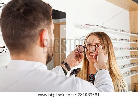 Friendly Male Ophthalmologist Choosing Eyeglass Frame For Beautiful Young Woman In An Optical Store