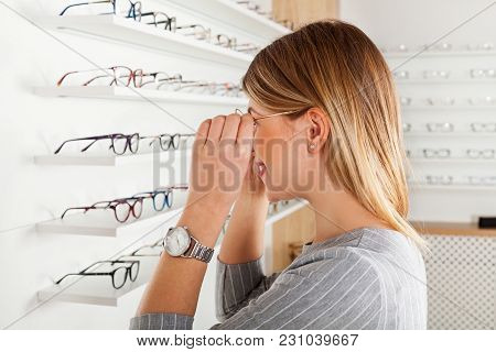 Young Woman Choosing Eyeglass Frame In An Optics Store, Checking In The Mirror, Side View