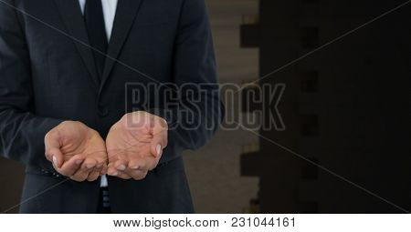 Digital composite of Businessman with hands palm open and dark background