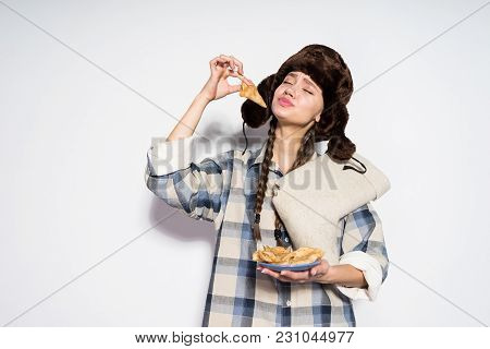 A Funny Young Russian Girl Eats Hot Delicious Pancakes, Fur Hat On Her Head, Celebrates Shrovetide