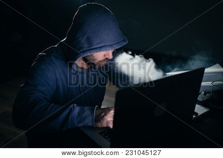 Mysterious Man Hacker In The Hood Doing Something Illegal On The Laptop, In The Dark, Smoking A Hook