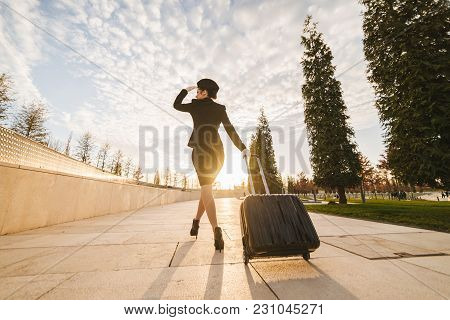 Slender Young Woman Stewardess In Uniform With A Suitcase Goes On A Flight, Outdoors In The Park