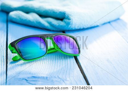 The modern sunglasses and blue towel on blue table.