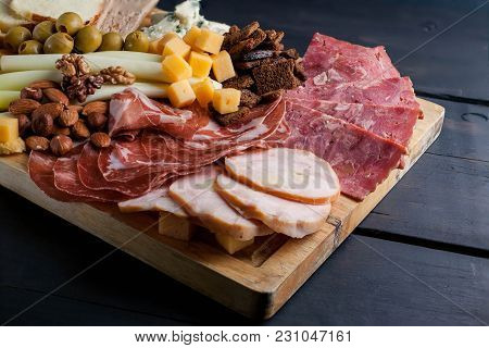 Assorted From Meat And Cheese On A Chopping Board. Smoked Sausage, Meat Roll From A Turkey With Chee