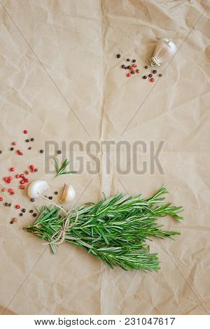 Bunch Of Rosemary With Garlic And Spices On Wrapping Paper. Copy Space Composition. Overhead Shots
