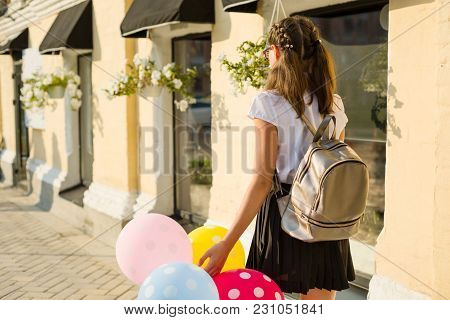 Back View. Girl Teenager High School Student With Balloons, In School Uniform Goes Along The City St