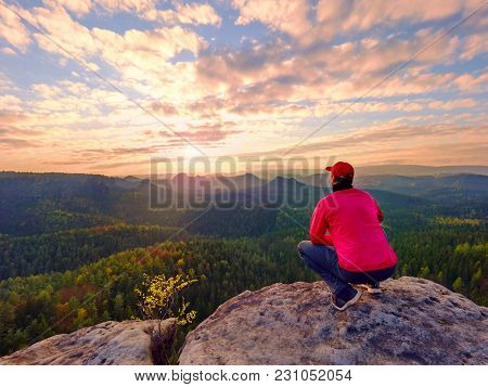 Hiker Man Take A Rest On Mountain Peak. Man Lay On Summit, Bellow Autumn Valley. Bright Morning Sun