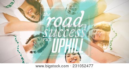 Cheerful group of volunteers putting hands together against the road to success run uphill