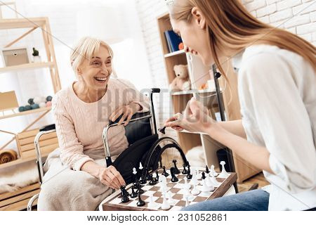 Girl Is Nursing Elderly Woman In Wheelchair At Home. They Are Playing Chess.