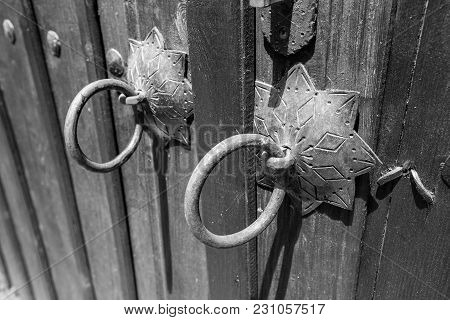 Black And White Image Of Close Up On Rusty Ornamented Metallic Door Ring Hoop On Vintage Old Wooden
