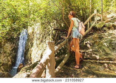 Young Woman And Waterfall In Tropical Rain Forest