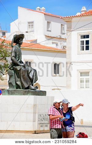 Lagos, Portugal - June 9, 2017 - A Couple Looking At A Map And Pointing In Front Of The Statue Of In
