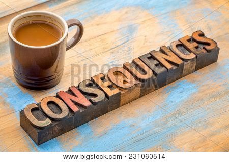 consequences- word abstract in vintage letterpress  wood type with a cup of coffee
