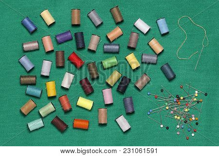 Needle , Pins And Sewing Thread On A Green Cloth