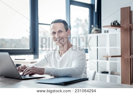 Adore My Work. Successful Qualified Satisfied Man Sitting By The Table Smiling And Using The Laptop.