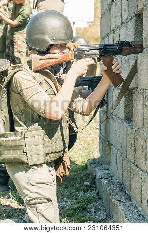 A Young Girl Soldier Shoots A Rifle From Behind A Wall