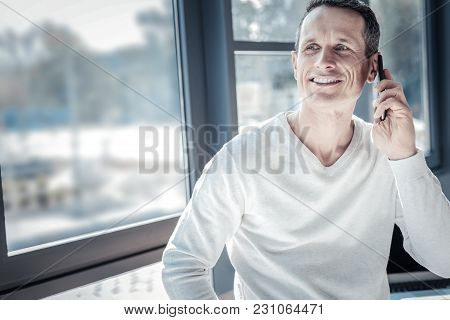Good News. Satisfied Handsome Perspective Worker Standing In The Bright Room Looking Aside And Using