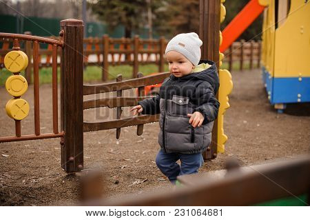 Little Boy Dressed In Warm Clothes Walking On The Playground On The Cloudy Autumn Day