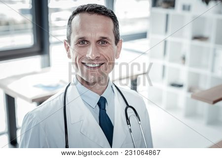 Im Ready. Reliable Confident Qualified Doctor Standing In The Cabinet Looking Straight And Smiling.