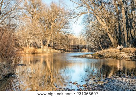 Fort Collins, CO, USA - March 10, 2018: A young couple is enjoying a warm early spring afternoon on a shore of Cache la Poudre RIver.