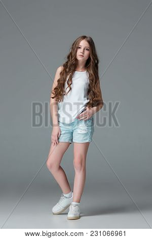 Full Length Of Young Slim Female Girl In Denim Shorts On Gray Studio Background. Studio Portrait Of