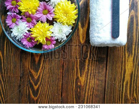 Spa Manicure With A Tray Of Flowers On A Wooden Background And A White Fluffy Towel