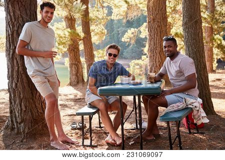 Three male friends at a table by a lake smiling to camera, close up