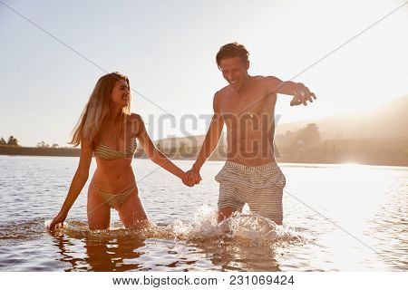 Young white couple holding hands in a lake at sundown
