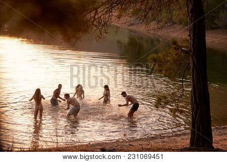 Young adult friends splashing and having fun in a lake